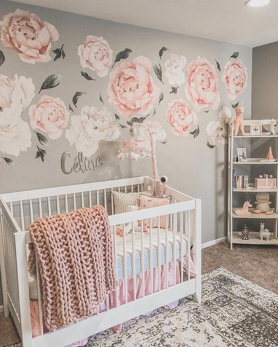 a chic girl's nursery with a pink floral mural, grey walls, white furniture and touches of pink here and there