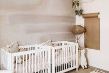 a chic twin nursery with a watercolor wall, white furniture, a rattan chandelier and rattan and paper touches