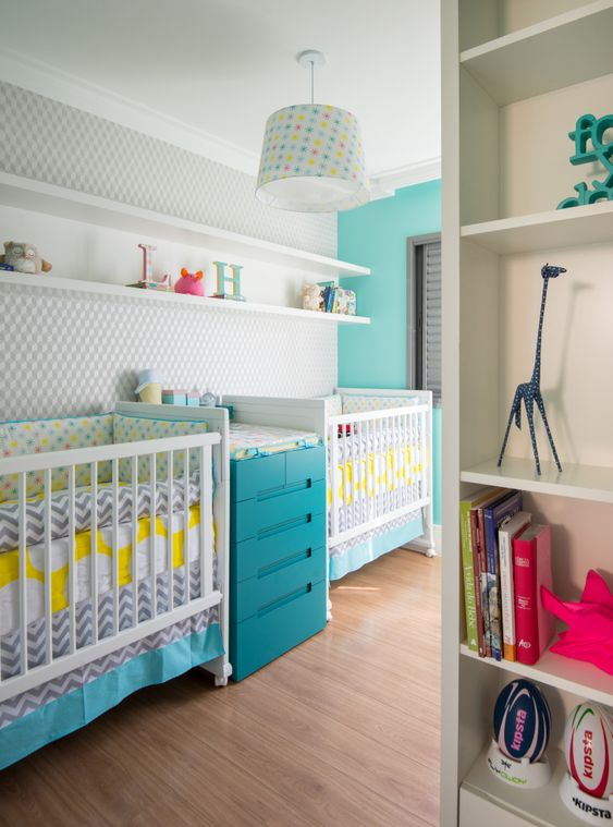 a colorful shared nursery with a grey wall, white furniture, a blue changing table, floating shelves and a colorful chandelier