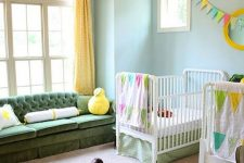 a colorful shared nursery with blue walls, white and green furniture, touches of bright yellow and bright printed textiles