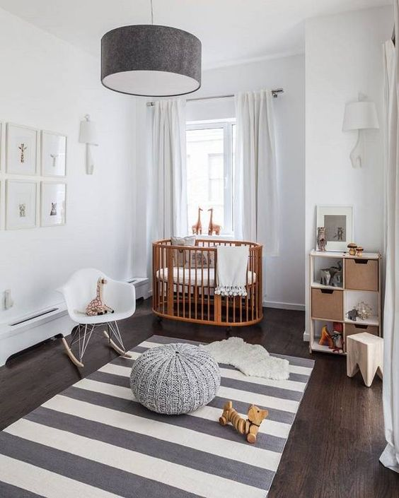 a contemporary nursery with a striped rug, a grey lamp and ottoman, a gallery wall and a cool stained crib