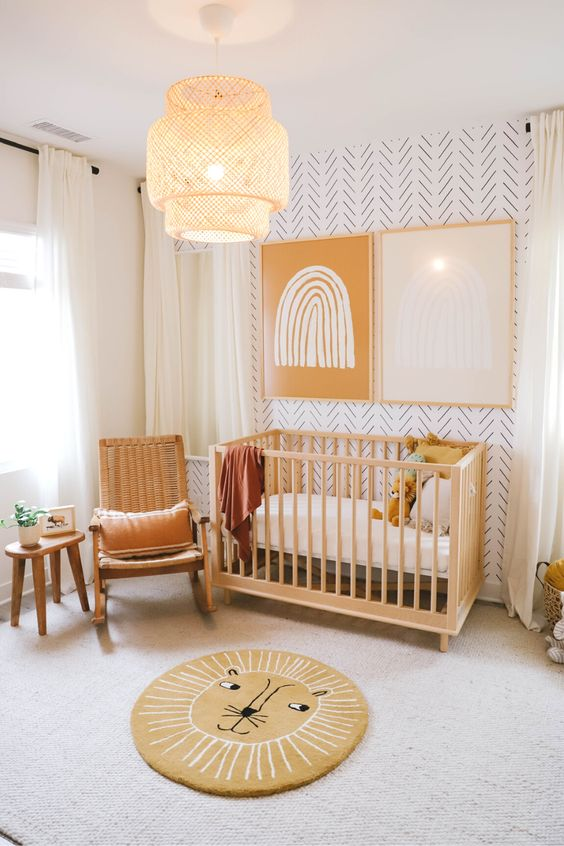 a cozy and warm colored nursery with a printed wall, wooden furniture, a fun rug and bold art on the wall