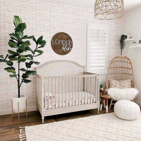 a cozy modern nursery with wallpaper walls, a sign, wicker chairs and a lampshade, potted greenery
