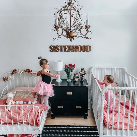 a cute black and white shared room with white beds, pink bedding and whimsy and chic details