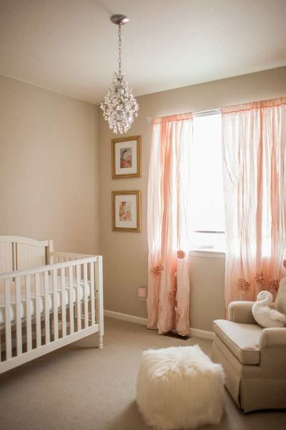 a cute girl nursery done in warm neutrals, with pink curtains with fluffs, a crystal chandelier and neutral bedding