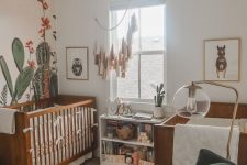 a desert themed nursery with stained cribs, a hunter green chair, a tassel hanging and a cactus accent wall