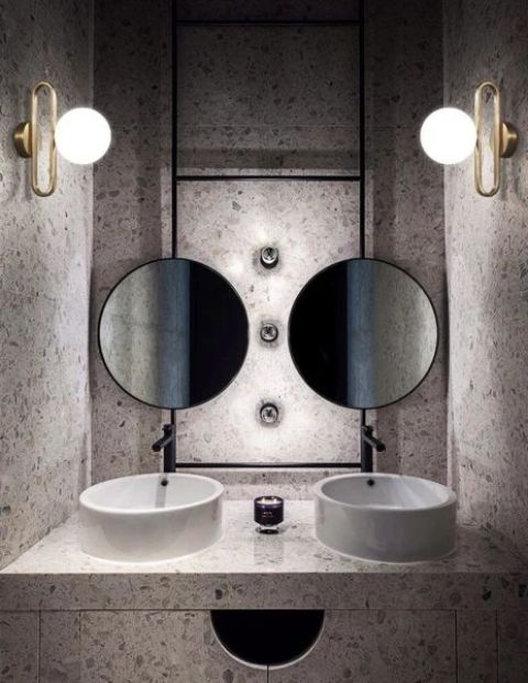 a duo of brass and glass sphere wall lamps echoes with round mirrors and sinks and looks hot