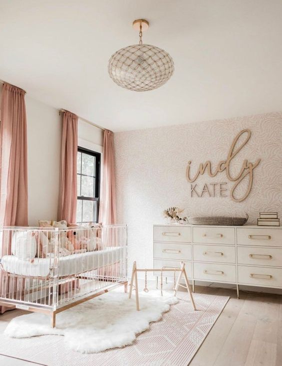 a fabulous modern girl nursery with a wallpaper wall, neutral dresser, an acryclic crib, a glass chandelier and pink textiles