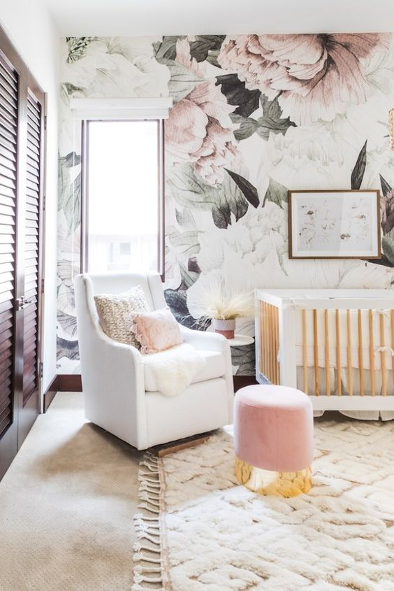 a glam and cute girlish nursery with a floral accent wall, white furniture and a pink ottoman plus a shutter wardrobe is cool