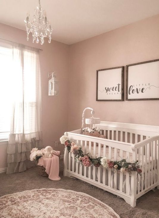 a glam girl's nursery with pink walls, white furniture, framed artworks, a floral garland and a crystal chandelier