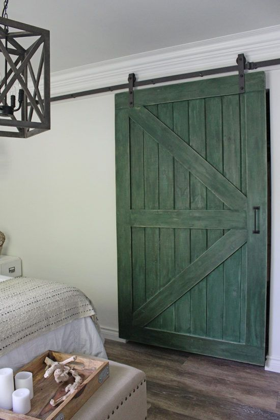 a green sliding barn door adds color and rustic chic to the space