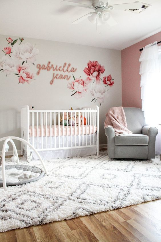 a grey and mauve nursery with a floral mural, a mauve wall, white and grey furniture and pink textiles
