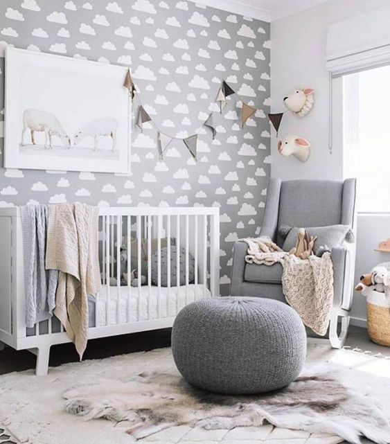 a grey gender neutral nursery with a cloud accent wall, chic white and grey furniture and garlands and faux taxidermy