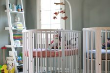 a grey nursery with white furniture, colorful and printed linens and a bookshelf with colorful books and toys