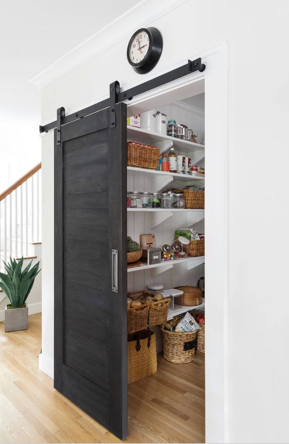 a grey sliding barn door hides the pantry and saves the space very well