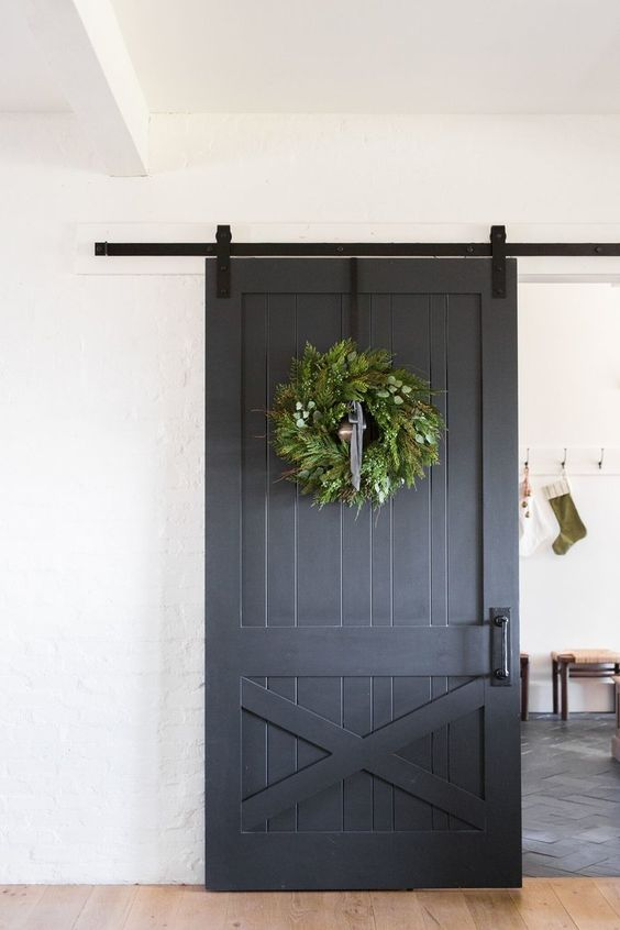 a grey sliding barn door with handles with a large greenery wreath brings a cheer holiday feel