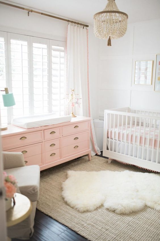 a lively girl nursery in white, with white and pink furniture, layered rugs, pink and white bedding and a beaded chandelier