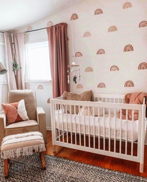 a lovely boho girl's nursery with a printed wall, simple neutral furniture, pink curtans and pink bedding