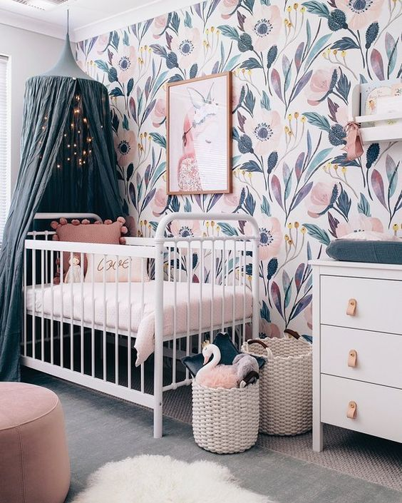 a lovely girl nursery with a beautiful floral mural wall, white furniture, a teal canopy and cushions, pink ottomans and baskets