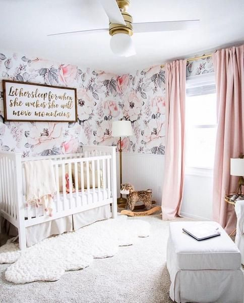 a lovely nursery with floral walls, white furniture, pink curtains, pretty modern lamps and layered rugs is cozy