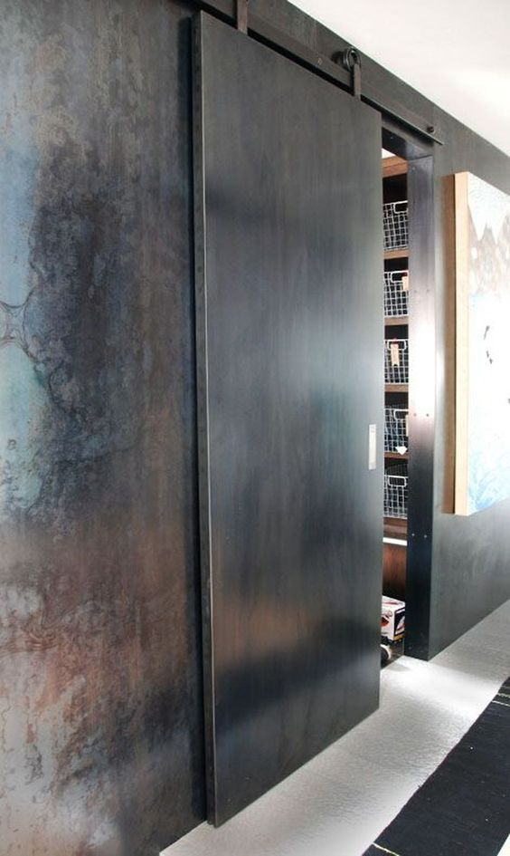 a metal sliding door continues the industrial and rough decor theme of the space