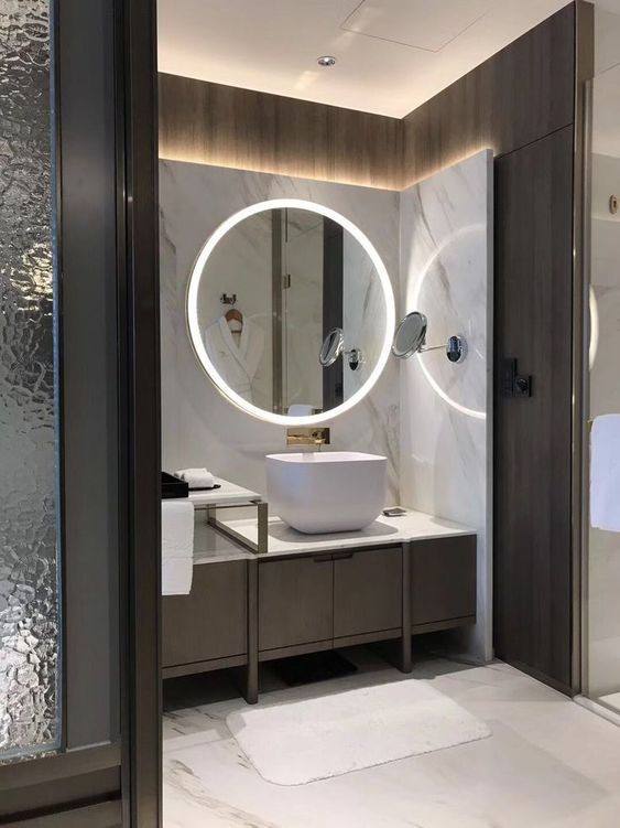 a minimalist bathroom with built-in lights in the mirror and wall around the vanity looks super chic and amazing