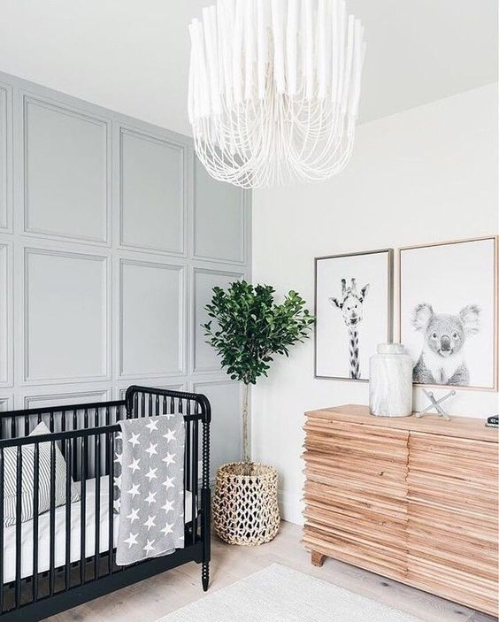 a modern gender neutral nursery with a grey paneled wall, a wooden sideboard, a black crib and a catchy chandelier