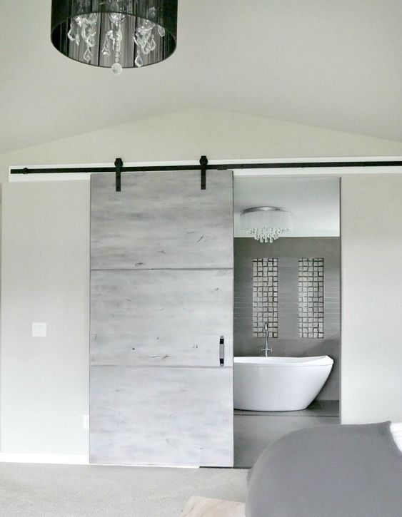 a modern grey sliding barn door for an ultra-modern space brings a rustic feel yet with a modern twist