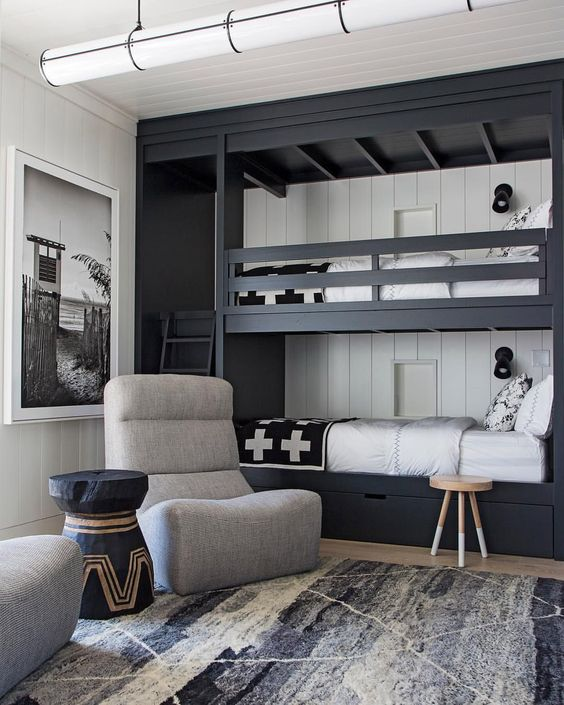a monochromatic shared boy bedroom with black bunk beds, drawers, grey chairs and a graphic rug