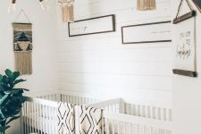 a neutral boho nursery with neutral furniture, printed linens, artworks and crochet chandeliers, a statement plant and touches of rattan