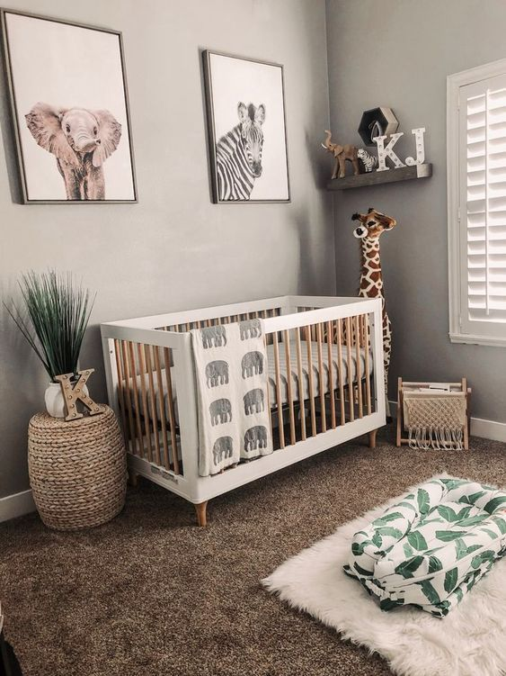 a neutral jungle-themed nursery with wooden furniture, layered rugs, an open shelf and a gallery wall