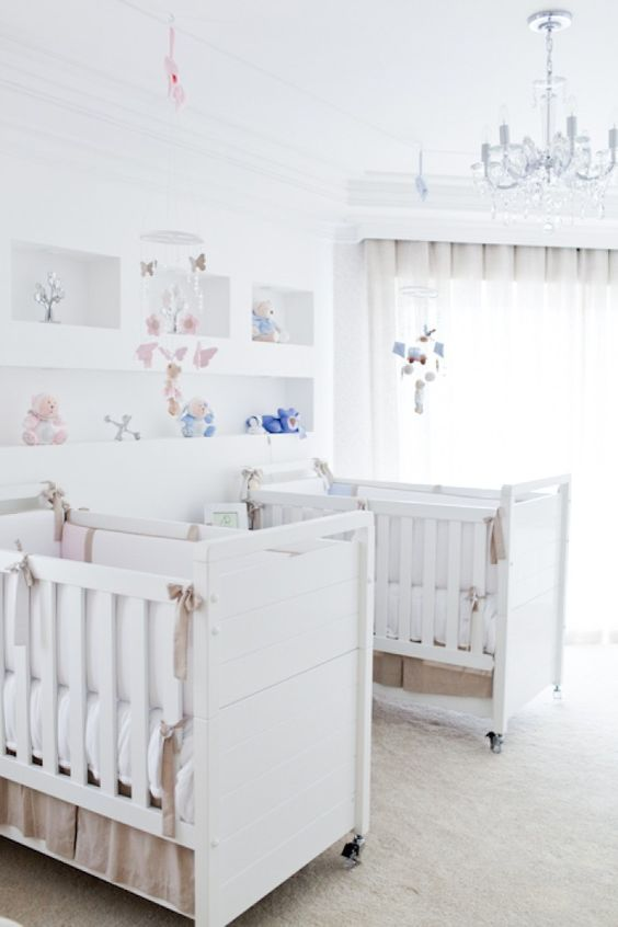 a neutral shared nursery with white furniture, open shelving, a crystal chandelier and pink and blue linens and toys