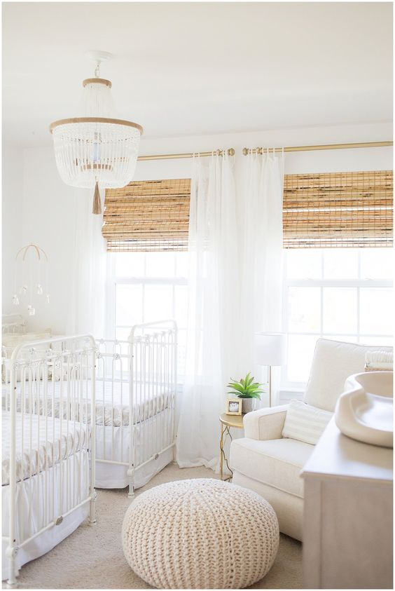 a neutral shared nursery with white furniture, woven shades, a beaded chandelier and a knit ottoman