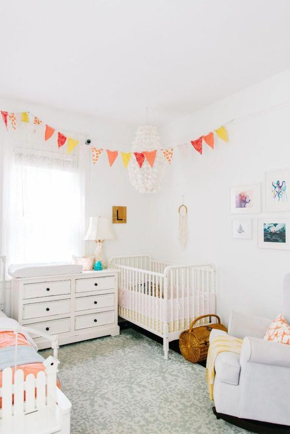 a neutral shared room with a couple of bright touches   a colorful bunting and bedding for a chic look