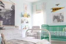 a pastel shared nursery with light blue walls, a green crib, a white bed and other furniture and cool artworks