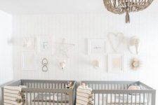 a peaceful twin nursery with grey cribs, a beaded chandelier, gallery walls and neutral bedding is relaxing