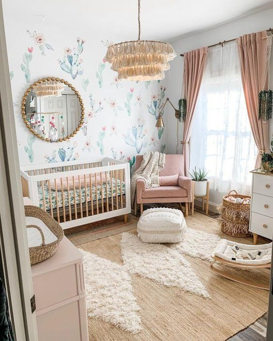 a pretty boho girlish nursery with a cactus wall, neutral and pink furniture, pink bedding and curtains, a tassel chandelier and a lovely boho rug
