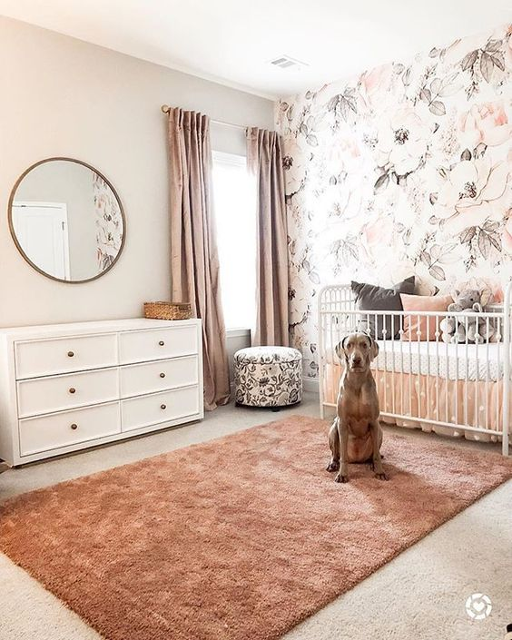 a pretty girlish nursery with a floral accent wall, white furniture, a floral ottoman, pink curtains and a peachy pink rug