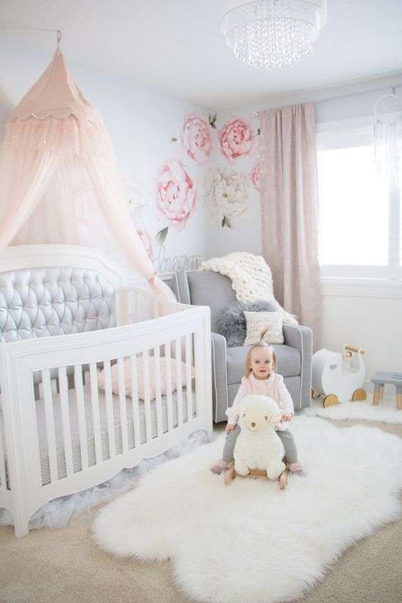 a pretty nursery with light blue walls, floral decals, white and grey furniture, a pink canopy and pink curtains plus a crystal chandelier