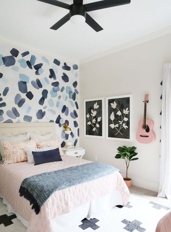 a pretty teen bedroom with a brushstroke accent wall, pink and blue textiles and a pink guitar on the wall