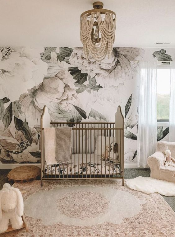 a refined girl nursery with a floral mural, a vintage brass crib, neutral and pink textiles and a beaded chandelier
