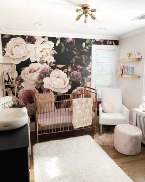 a refined moody girl nursery with a moody floral wall, white and black furniture, a brass crib, blush and white textiles