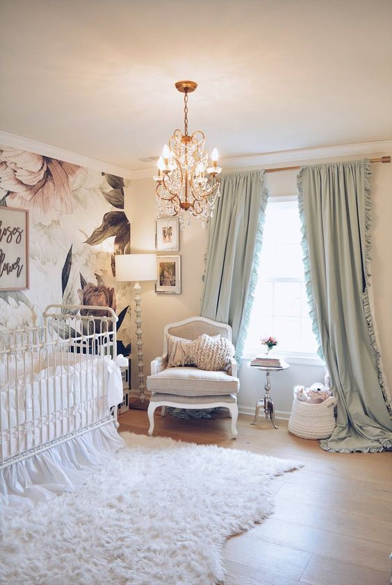 a refined nursery with a floral wall, vintage neutral furniture, a crystal chandelier, mint green curtains and a faux fur rug