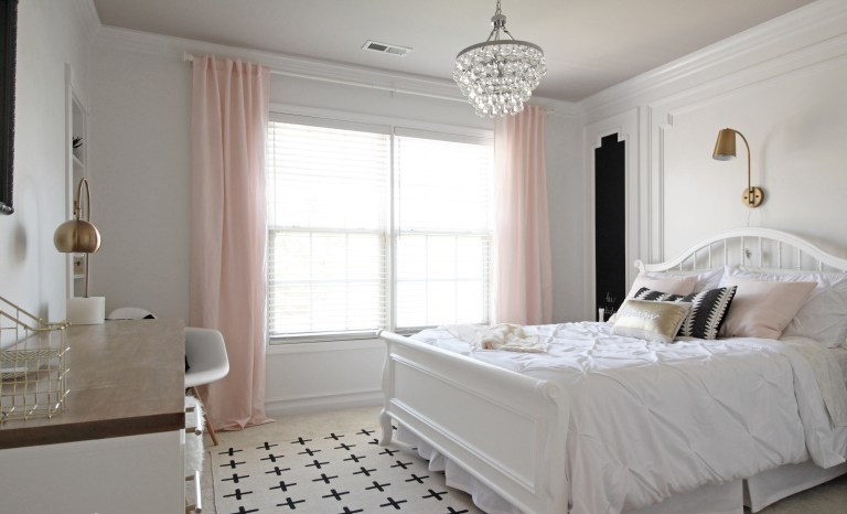 a refined teen girl bedroom in black, white and blush, with a large comfy bed, a crystal chandelier and touches of brass