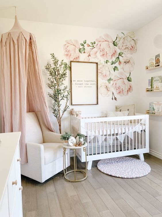 a romantic girlish nrusery with floral decals, white furniture, a pink canopy over the chair and some open shelves
