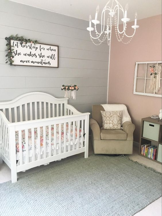 a rustic girlish nursery with a pink and grey wall, a lovely sign, white and taupe furniture, a vintage chandelier and some shabby chic decor
