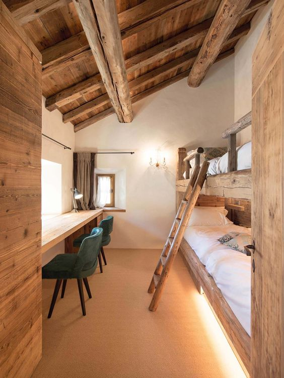 a rustic shared boy bedroom with rough wood bunk beds, a floating desk, woodne beams and a ladder