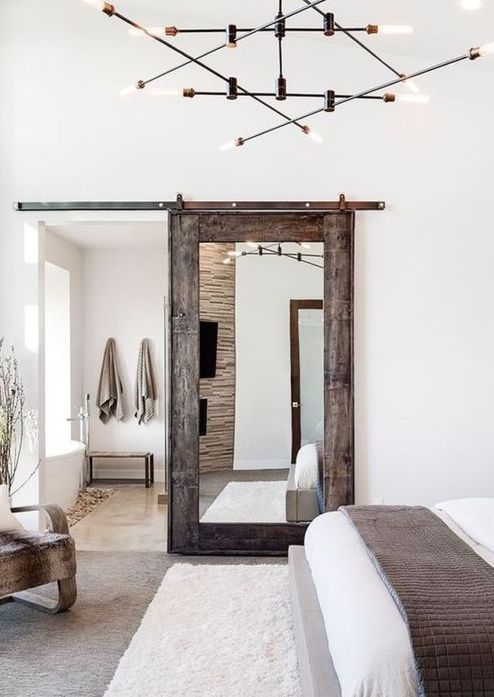 a rustic weathered wooden door with a large mirror brings a rustic feel and a cozy touch