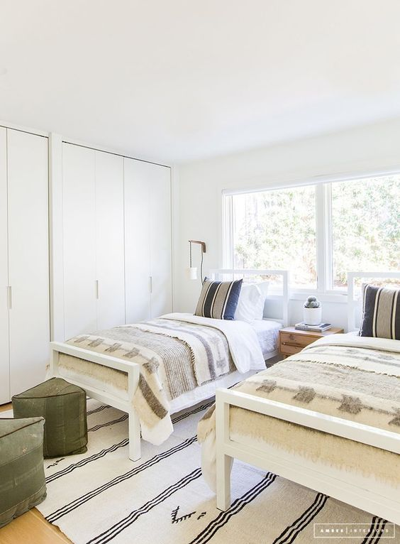 a serene shared boy bedroom in neutrals, with two beds, green ottomans and a large storage unit