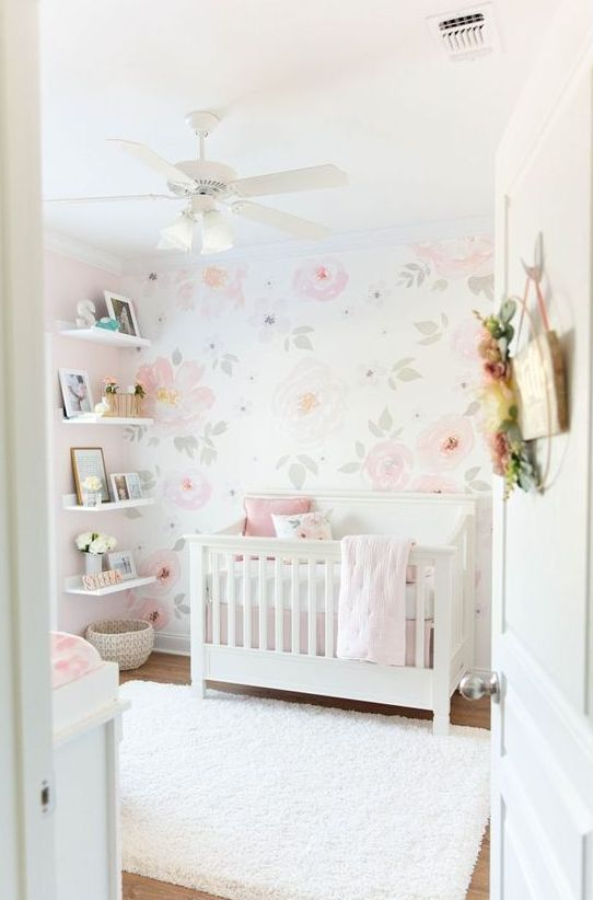a simple and chic girlish nursery with white furniture, a floral wall, open shelves and white and pink bedding